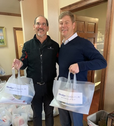 Charles Hodge and Ryan Langley holding bags with turkeys for the Thanksgiving Giveaway