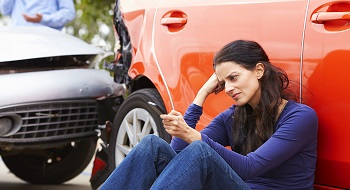 Upset woman checks insurance options after car accident